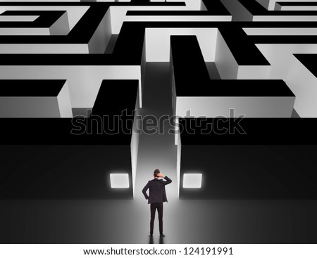 Business man in front of a huge maze thinking how to get through - stock photo