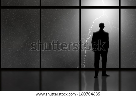 Business Man in high rise office looking out at a lightning storm
