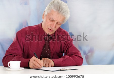 business man in maroon shirt sits on a white background