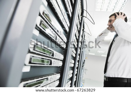 business man in network server room have problems and looking for  disaster solution - stock photo