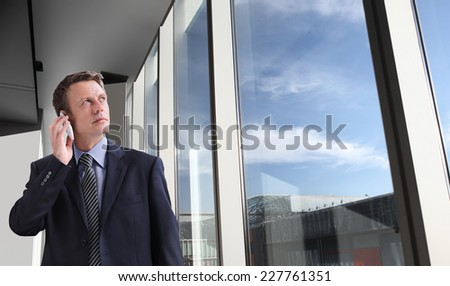 business man in office talking on the phone and looks through the window at the sky with clouds - stock photo