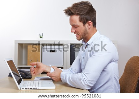 Business man in office with RSI syndrome holding his aching hand - stock photo