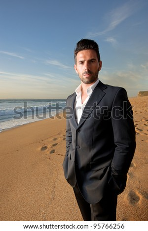 business man in suit at sunset at the beach - stock photo