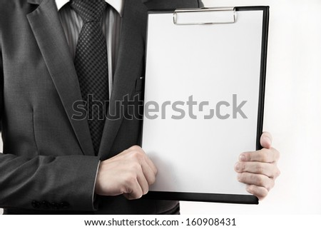 Business man in suit holding a blank clipboard. isolated on white - stock photo