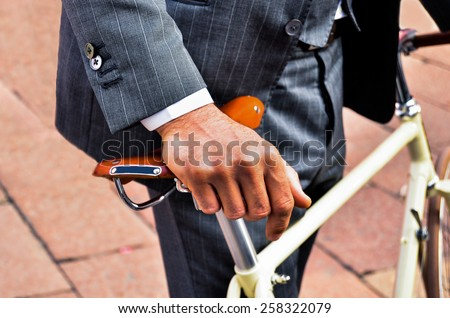 Business man in suit holding a vintage bicycle - stock photo