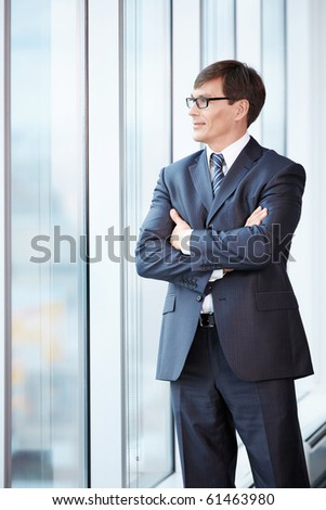 Business man in suit looking out the window - stock photo