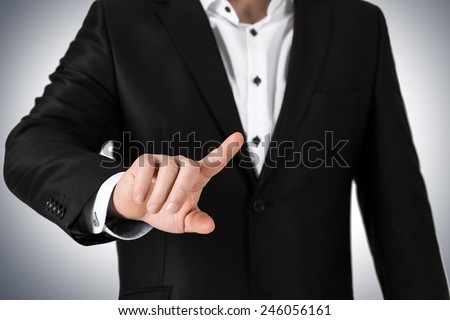 Business man in  suit pressing on blank button.