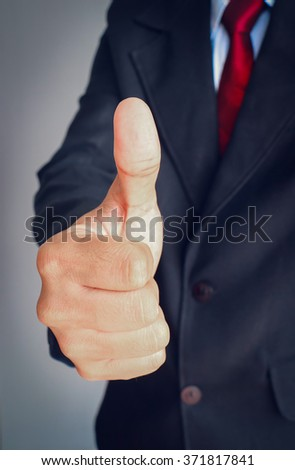 Business man in suit with red tie showing thumbs up sign on gray background. - stock photo