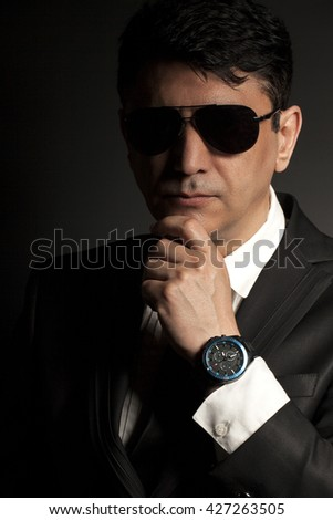 Business man in suit with sunglasses on a black background