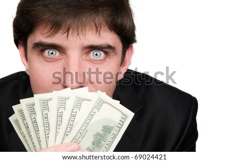 Business man in suit with wide open eyes covering his mouth with one hundred dollars banknotes