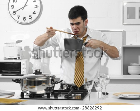 business man in the kitchen that it tastes what he cooked - stock photo