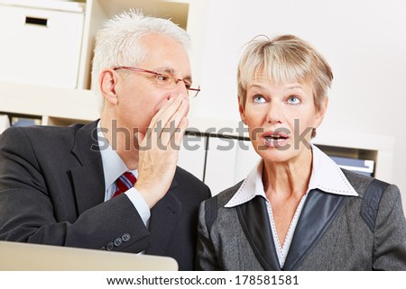 Business man in the office whispering a secret into ear of surprised woman - stock photo