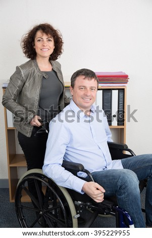 Business man in wheelchair with assistant in office - stock photo