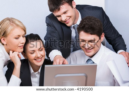 Business man is explaining the correct way of analysis to his colleagues in  the office pointing at the monitor - stock photo