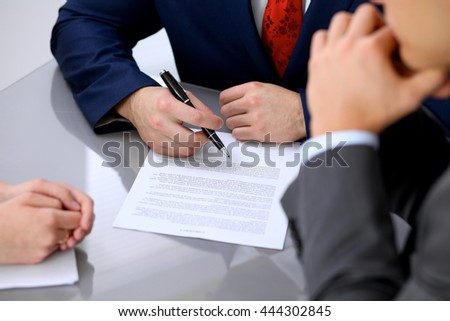 Business man is going to sign contract. Group of business people at meeting