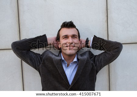 Business man is leaning against the wall with hands on head, happy, thinking about the future.   - stock photo