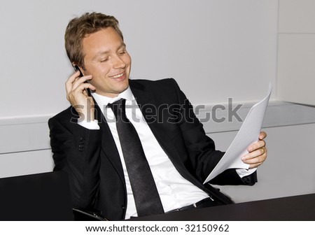 Business man is sitting and looking satisfied calling on the phone and holding a contract in the other hand