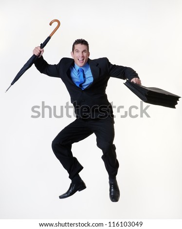 business man jumping in the air holding a umbrella and briefcase