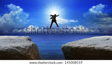 business man jumping to next cliff with risk decision - stock photo