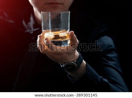 Business man keeps the whiskey glass with ice in his hand