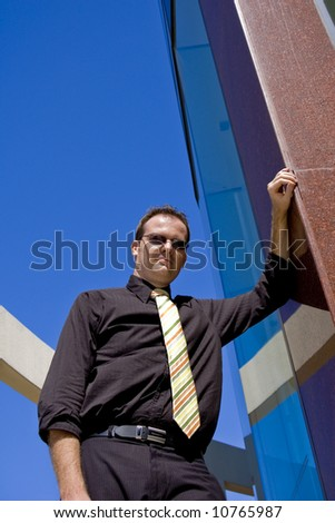 Business man leaning against a tall building
