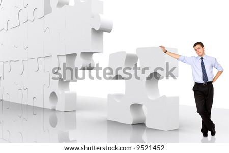 business man leaning on a puzzle piece - good concept for business solutions isolated over a white background - stock photo