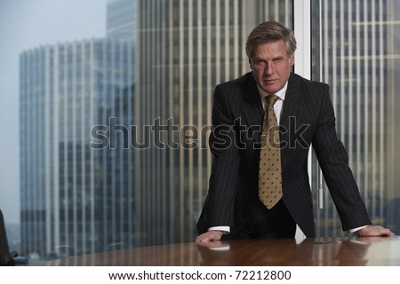Business man leaning on table in boardroom looking at camera