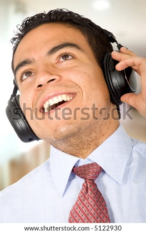 Business man listening to music in his office - stock photo