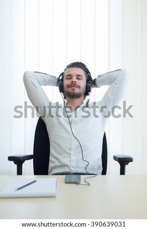 business man listens to music with headphones in a office