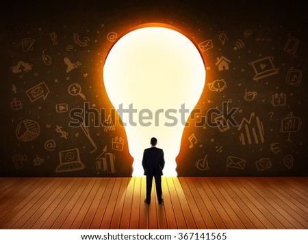 Business man looking at bright light bulb in the wall concept