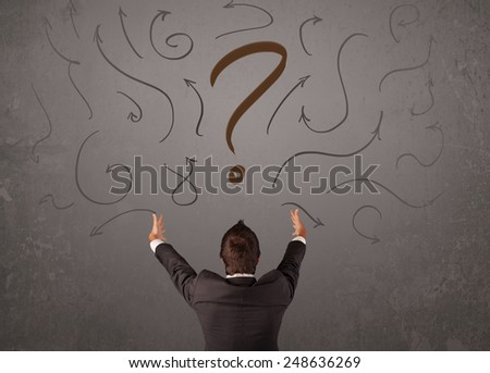 Business man looking at question mark sketch on the wall - stock photo