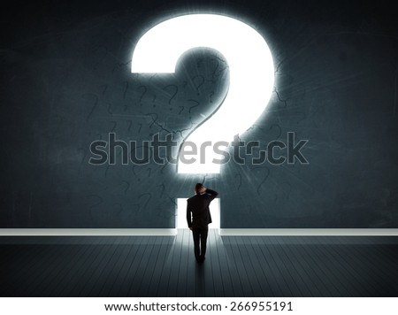 Business man looking at wall with a bright question mark concept - stock photo