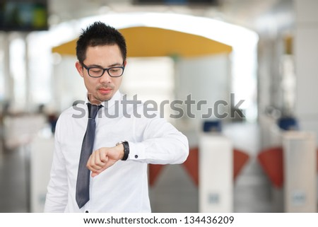 Business man looking at watch at business center - stock photo