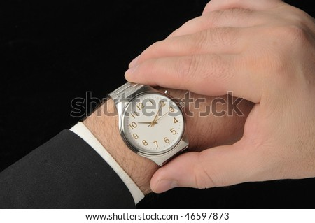 Business man looking at watch. Black Background - stock photo