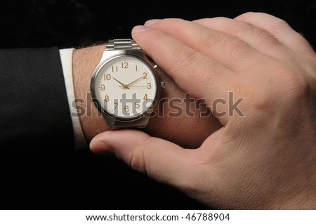 Business man looking at watch. Black Background