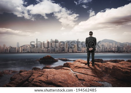 Business man looking city from the rocks - stock photo