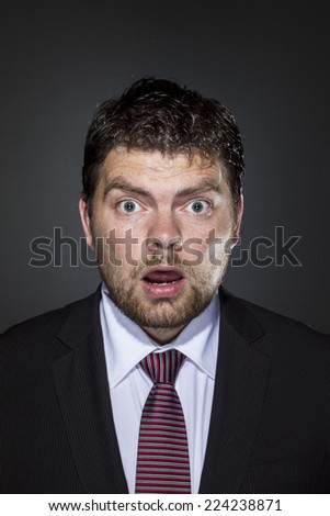 business man looking surprised on a dark gray background