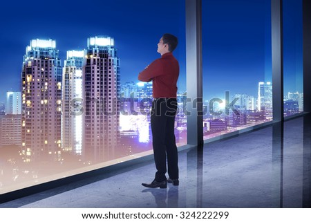 Business man looking the city from his office room. Business success concept