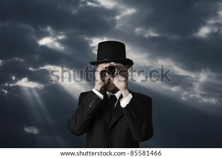 business man looks through a telescope in darkness - stock photo
