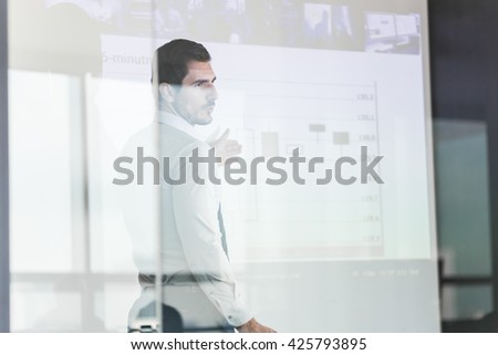 Business man making a presentation in front of whiteboard. View through glass. - stock photo