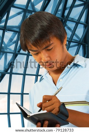 Business Man Making Notes In His Planner At A Convention Center - stock photo