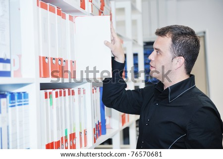 business man male adult in archive library looking and searching for book and documents representing storage and education concept - stock photo