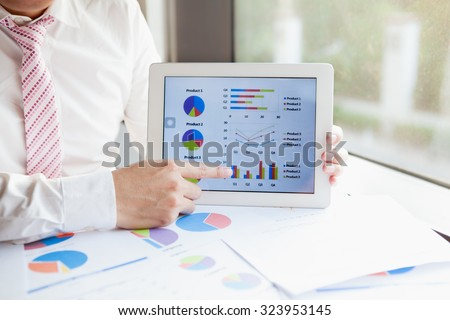 Business man meeting/present on tablet to discuss the situation on the market with product this year. - stock photo