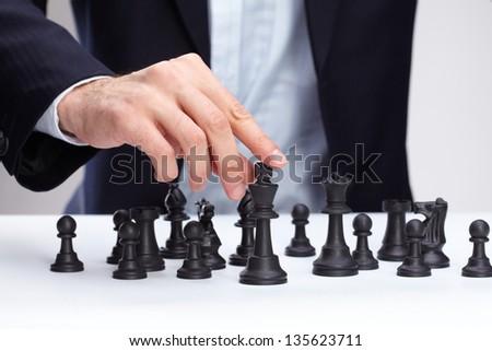 Business man moving chess figure - stock photo