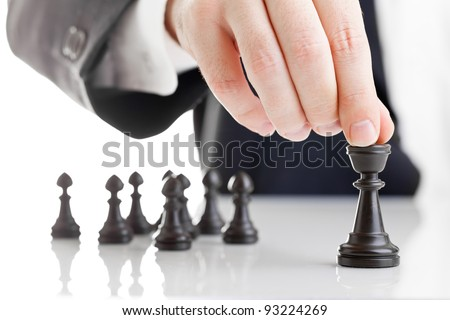 Business man moving chess figure with team behind - strategy or leadership concept - stock photo