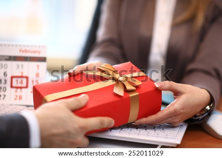 Business man offering a gift to a woman - stock photo