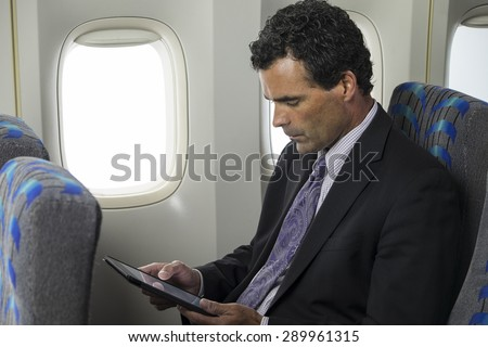Business man on a plane using an ipad/tablet - stock photo