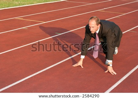 Business man on a red running track in the start position ready to run - stock photo