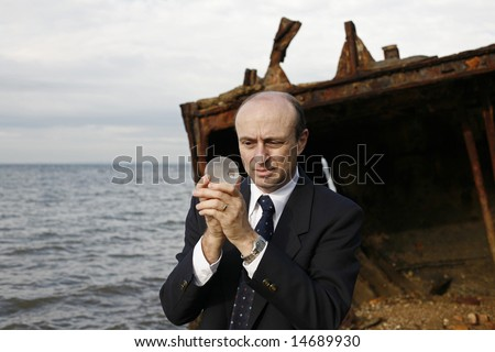 Business man on a ship wreck gazing at a glass globe. - stock photo