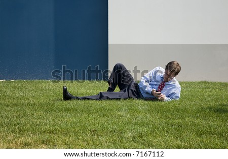 Business Man on Blackberry Phone while Laying Down - stock photo